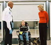 Photo of a TSO standing next to a boy in a wheelchair, wih his mom next to him.